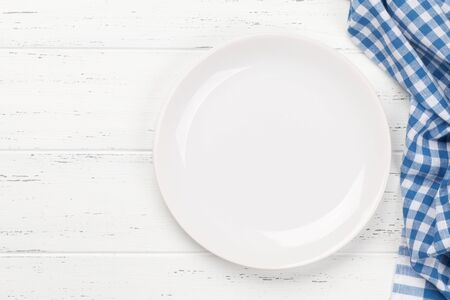 Kitchen table with empty plate, tablecloth and space for your recipe or menu. Top view flat lay Foto de archivo
