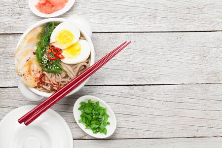 Asian noodle ramen soup with chicken, vegetables and eggs on wooden background. Top view flat lay with copy space 스톡 콘텐츠 - 140992720