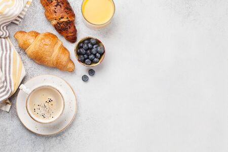 Breakfast with coffee, orange juice and croissant. Top view on stone table. Flat lay with copy space