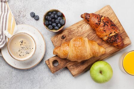 Breakfast with coffee, orange juice and croissant. Top view on stone table. Flat lay