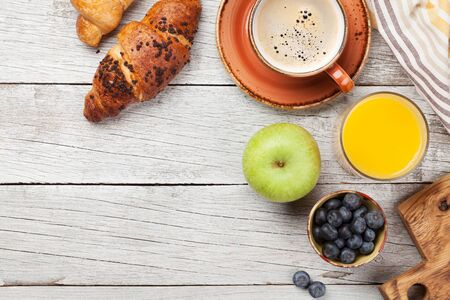 Breakfast with coffee, orange juice and croissant. Top view on wooden table. Flat lay with copy space