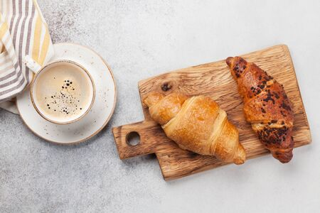 Breakfast with coffee and croissant. Top view on wooden board. Flat lay