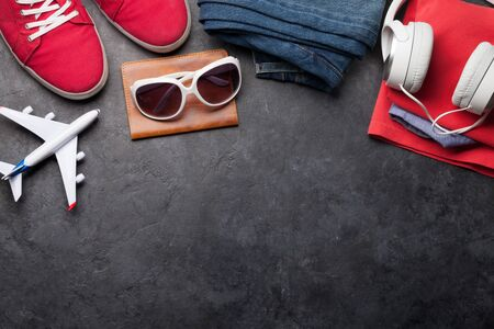 Clothing and accessories. Sneakers, jeans and headphones. Urban outfit for everyday or travel vacation on stone background with copy space. Top view flat lay 版權商用圖片
