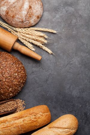 Various bread with wheat, flour and cooking utensils on stone table. Top view flat lay with copy space 스톡 콘텐츠 - 140992591