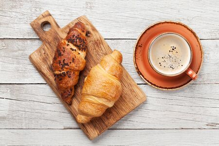 Breakfast with coffee and croissant. Top view on wooden table. Flat lay Stock fotó