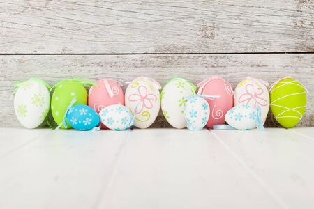 Easter greeting card with colorful easter eggs in front of wooden wall. With space for your greetings
