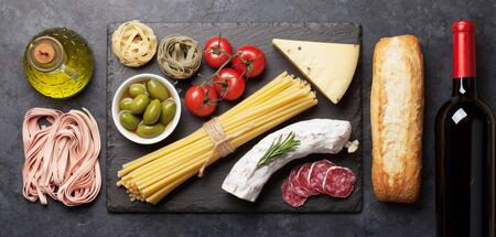 Italian cuisine food ingredients. Pasta, cheese, salami, olives and wine. Top view flat lay on stone table 版權商用圖片