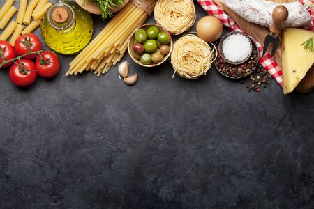 Italian cuisine food ingredients. Pasta, cheese, salami, olives and tomatoes. Top view flat lay on stone table with copy space