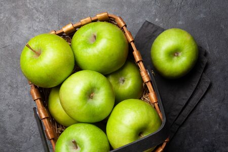 Ripe green apple fruits in basket on dark stone table. Top view. Flat lay
