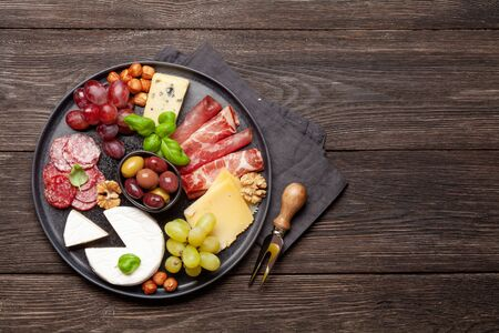 Cheese, meat, grapes and olives antipasto. Appetizer selection on plate. Top view with copy space. Flat lay Standard-Bild