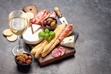 Cheese, meat, grapes and nuts antipasto. Appetizer selection on plate and glass with white wine. With copy space