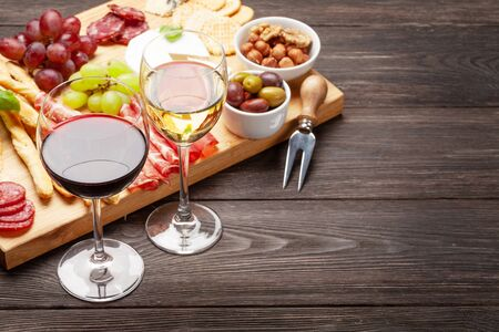 Cheese, meat, grapes and olives antipasto. Appetizer selection on wooden board and glasses with red and white wine. With copy space