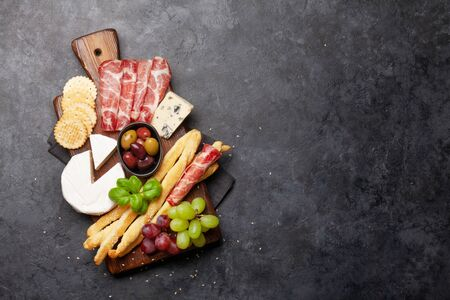 Cheese, meat, grapes and olives antipasto. Appetizer selection on wooden board. Top view with copy space. Flat lay Standard-Bild