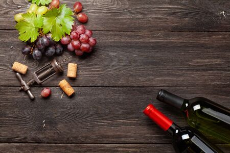 Various grapes, wine bottles and corkscrew on wooden table. Top view with copy space. Flat lay