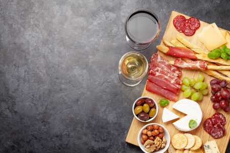 Cheese, meat, grapes and olives antipasto. Appetizer selection on wooden board and glasses with red and white wine. Top view with copy space. Flat lay Standard-Bild