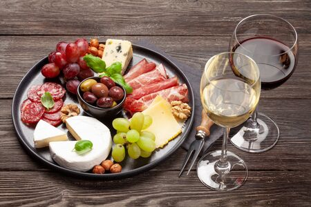 Cheese, meat, grapes and olives antipasto. Appetizer selection on plate and glasses with red and white wine