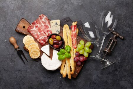 Cheese, meat, grapes and olives antipasto. Appetizer selection on wooden board. Top view flat lay Standard-Bild