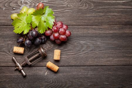 Various grapes and wine corkscrew on wooden table. Top view with copy space. Flat lay