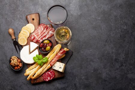 Cheese, meat, grapes and nuts antipasto. Appetizer selection on plate and glasses with red and white wine. Top view with copy space. Flat lay Standard-Bild