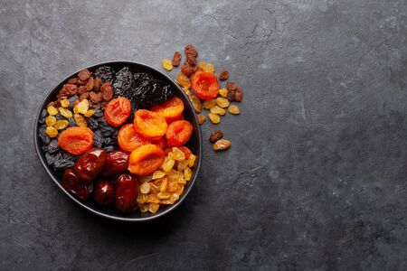 Various dried fruits and nuts on a dark stone table. Top view with copy space