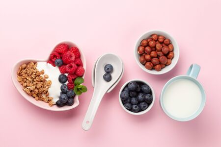 Healthy breakfast with homemade granola with yogurt and fresh berries on pink background. Top view