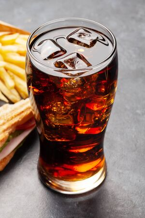 Glass of cola drink with ice, club sandwich and potato fries chips. Fast food take away Standard-Bild