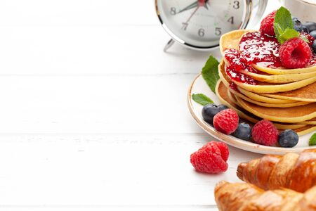 Delicious homemade pancakes with summer berries and jam, croissants and coffee for breakfast. Morning meal concept with copy space Standard-Bild