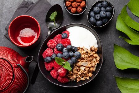 Healthy breakfast with homemade granola with yogurt and fresh berries on stone background. Top view flat lay