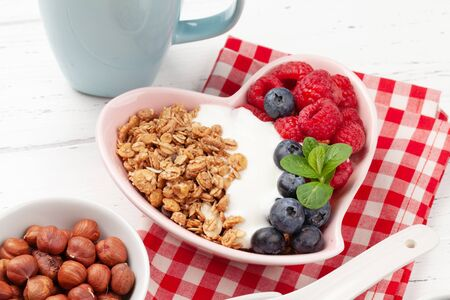 Healthy breakfast with homemade granola with yogurt and fresh berries on wooden background Standard-Bild