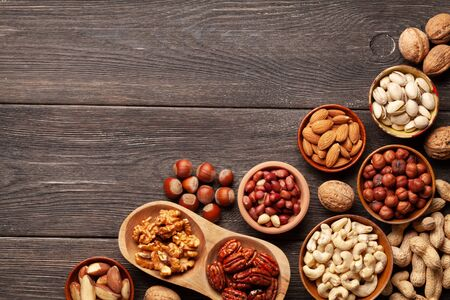 Various dried fruits and nuts on a dark wooden table. Top view flat lay with copy space Standard-Bild