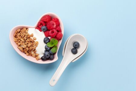 Healthy breakfast with homemade granola with yogurt and fresh berries on blue background. Top view with copy space