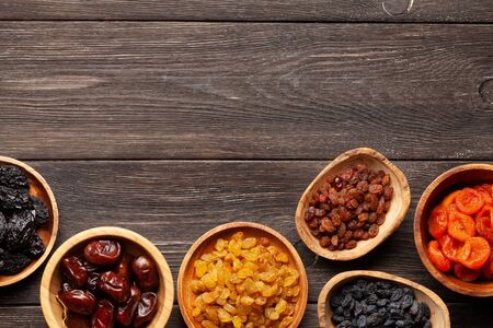 Various dried fruits on a dark wooden table. Top view flat lay with copy space Standard-Bild
