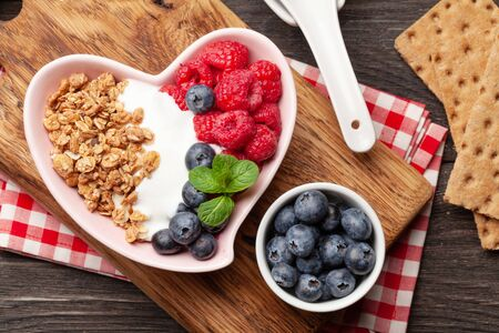 Healthy breakfast with homemade granola with yogurt and fresh berries on wooden background. Top view flat lay