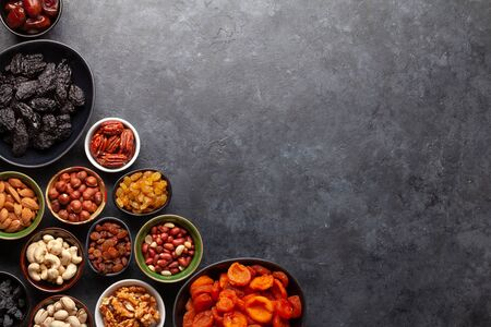 Various dried fruits and nuts on a dark stone table. Top view flat lay with copy space