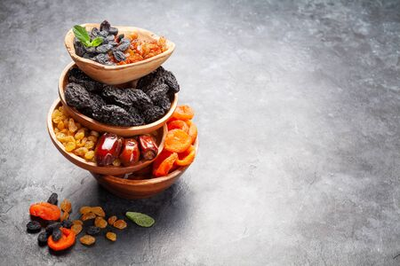 Various dried fruits and nuts on a dark stone table. With copy space