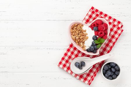 Healthy breakfast with homemade granola with yogurt and fresh berries on wooden background. Top view with copy space