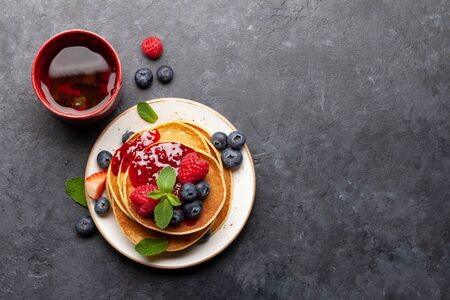 Delicious homemade pancakes with summer berries and tea for breakfast. Top view with copy space