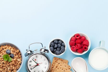 Healthy breakfast with homemade granola with yogurt and fresh berries on blue background. Morning meal concept. Top view with copy space