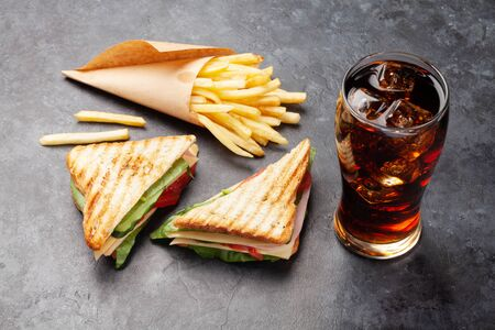 Club sandwich, potato fries chips and glass of cola drink with ice. Fast food take away