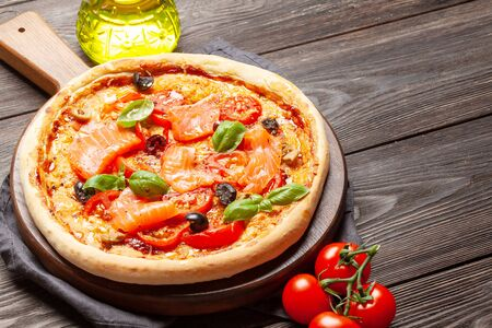 Tasty homemade seafood pizza with garden tomatoes, cheese, salmon and basil. With copy space Standard-Bild
