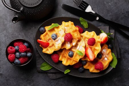 Delicious belgian waffles with ice cream and summer berries and breakfast tea. Top view