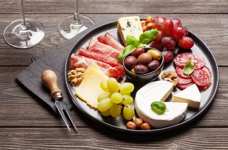 Cheese, meat, grapes and olives antipasto. Appetizer selection plate
