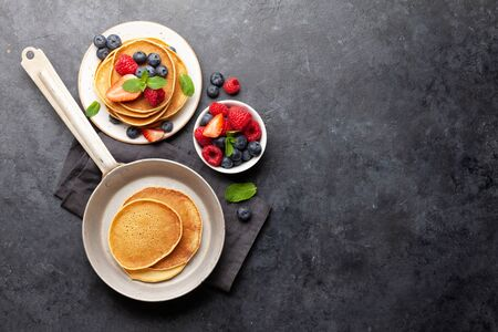 Delicious homemade pancakes with summer berries. Top view with copy space
