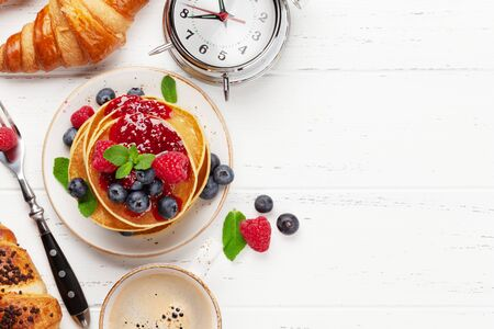 Delicious homemade pancakes with summer berries and coffee for breakfast. Top view with copy space