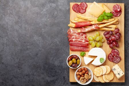 Cheese, meat, grapes and olives antipasto. Appetizer selection board. Top view with copy space. Flat lay