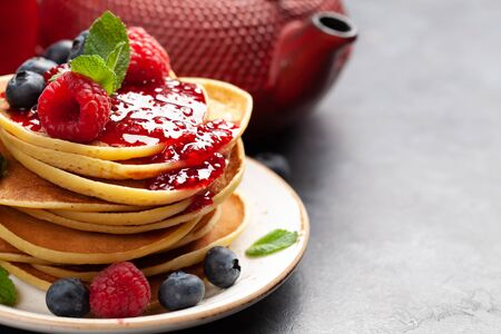 Delicious homemade pancakes with summer berries and tea for breakfast. With copy space