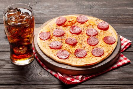 Tasty homemade pizza with pepperoni and glass of cola with ice Standard-Bild