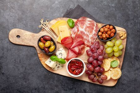 Cheese, meat, grapes and olives antipasto. Appetizer selection on wooden board. Top view. Flat lay