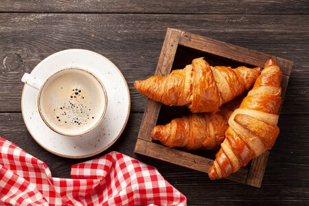 Coffee and croissants on wooden table. Breakfast meal. Top view Standard-Bild