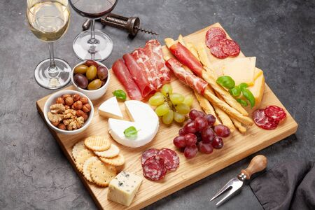 Cheese, meat, grapes and olives antipasto. Appetizer selection plate and glasses with red and white wine